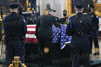 Photo - US Capitol Police officer Ken Shaver who was injured in the attack that killed US Capitol Police officer William Billy Evans touches the casket as he lies in honor at the Capitol in Washington Tuesday April 13 2021 Credit Jacquelyn Martin  Pool via CNPAdMedia