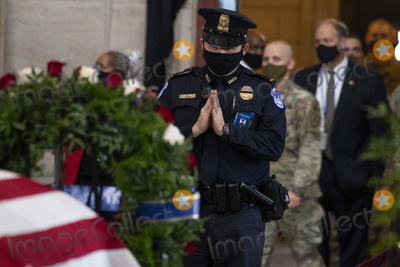 Photo - UNITED STATES - APRIL 13 A US Capitol Police Officer pays respects to Capitol Officer William Billy Evans as his remains lie in honor in the Capitol Rotunda in Washington DC on Tuesday April 13 2021 Evans was killed when a driver rammed the north barricade of the Capitol on April 2 2021 Credit Tom Williams  Pool via CNPAdMedia