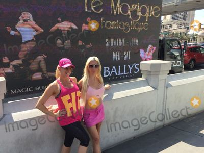 Photo - Frenchy Morgan and Suzie Malone Pose in front of billboards and ads for their new Las Vegas show Le Magique Fantastique