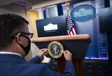 Mark Andes Photo - Communications staff installs the presidential seal on the lectern prior to President Donald Trump delivering remarks on the stock marked and the Dow reaching 30000 for the first time in history at the White House in Washington DC on Tuesday November 24 2020 Credit Kevin Dietsch  Pool via CNPAdMedia